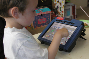 photo of a little boy with a PRC Vantage AAC device